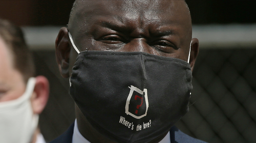 "Civil rights attorney Ben Crump wears a face mask with the words ""Where's the love?"" after announcing Wednesday, July 15, 2020 in Minneapolis the filing of a civil lawsuit against the city of Minneapolis and the officers involved in the death of George Floyd. Floyd died at the hands of police during an arrest on Memorial Day. (AP Photo/Jim Mone)"