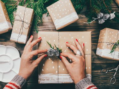 Woman wrapping Christmas presents in brown paper