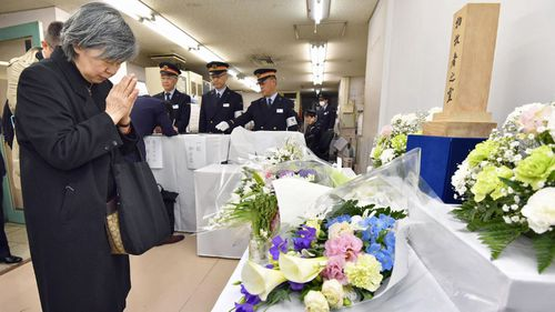 Shizue Takahashi, the wife of a subway worker killed in the March 20, 1995 sarin gas attack, prays after laying flowers on the stand set up at Kasumigaseki subway station in Tokyo on Tuesday. (AP).