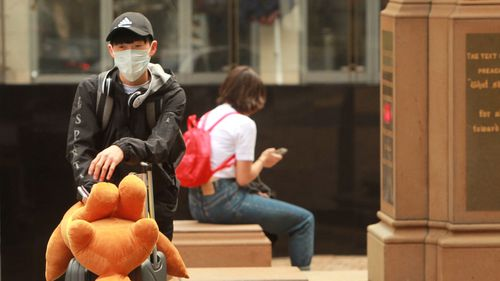 A young man wears a face mask in Sydney to prevent getting coronavirus.