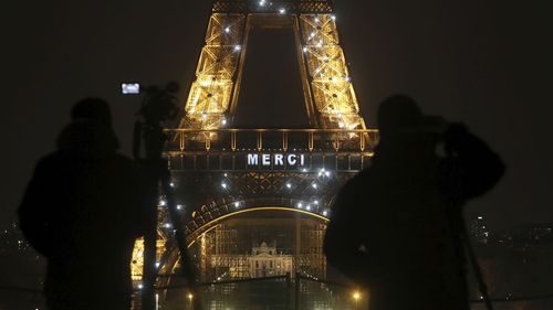 "Cameramen stand in front of the Eiffel Tower where the word ""Merci"", the French word for 'Thank you"", is emblazoned as France's coronavirus death toll continued to climb, in Paris, Friday, March 27, 2020"