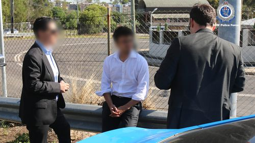 Mr Khawaja sits on a barrier while he is read his rights by officers.