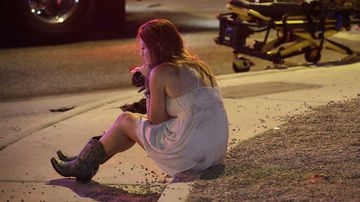 A survivor of the Las Vegas shooting sits alone on the kerb. (AAP)