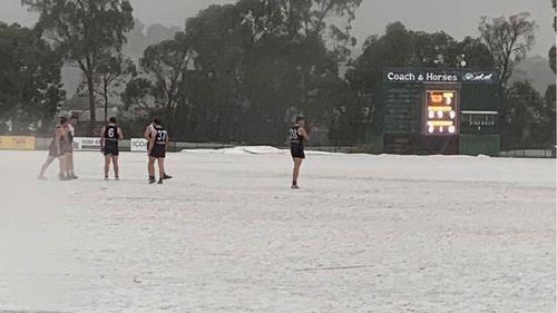 Football postponed as heavy hail blankets Melbourne, snow falling on alps