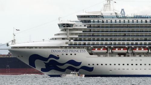 A small boat navigates near a cruise ship Diamond Princess anchoring off the Yokohama Port in Yokohama, near Tokyo.