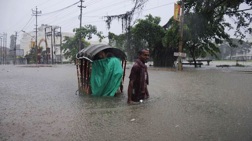 An Indian rickshaw puller transports a woman through a flooded street during a heavy downpour in Agartala. (AFP)