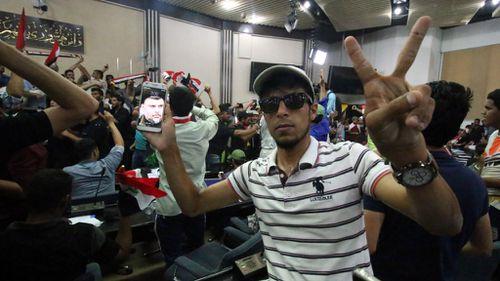 A protester displays an image of Moqtada al-Sadr on his smartphone inside the Iraqi parliament. (AFP)