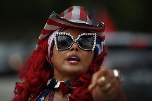 """Susy Tylor, who calls herself one of the """"Divas for Trump"""" greets other people arriving, as hundreds of cars gather ahead of the start of a car caravan in support of President Donald Trump, at Tropical Park in Miami"""