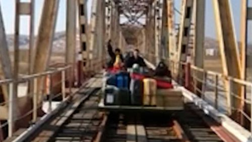 The Russian diplomat and his family crossing the bridge from North Korea into Russia.