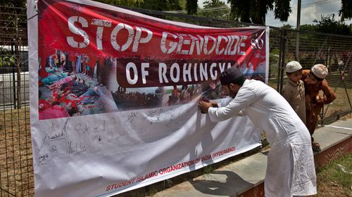 An Indian Muslim man puts his signature on a banner during a protest against the persecution of Myanmar's Rohingya Muslim minority. (AAP)