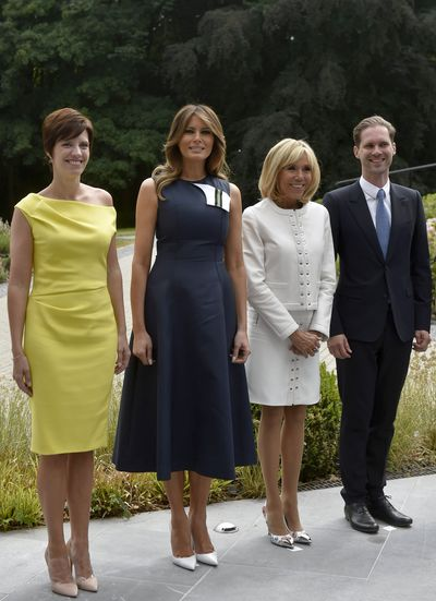 Melania Trump joined by the spouses of other NATO leaders donned  a navy sleeveless dress with a flared skirt by Calvin Klein in Brussels, July 2018