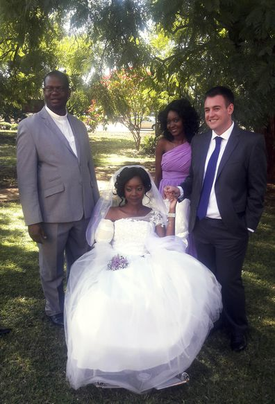 "In this photo taken on Saturday, May, 5, 2018, Zenele Ndlovu, center, and Jamie Fox hold hands on their wedding day at a hospital Chapel in Bulawayo, Zimbabwe. A couple attacked by a crocodile wedded days later in a Zimbabwean hospital, where the bride was recovering after losing an arm. ""In one week we went from shock and agony to a truly amazing experience,"" Fox told The Associated Press on Monday, May 7. (AP Photo)"