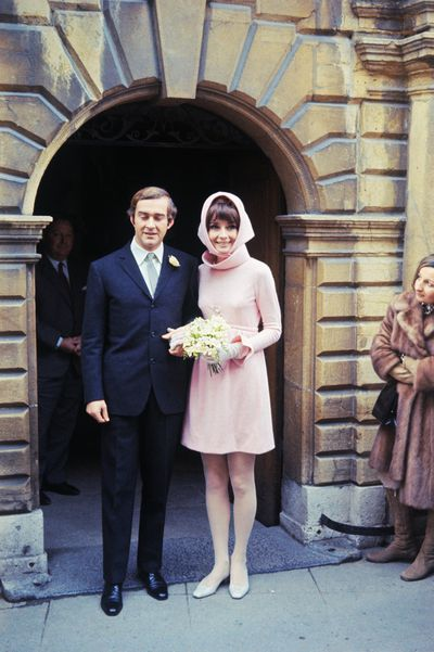 <p>Audrey Hepburn and Andrea Dotti,</p> <p>Dress: Givenchy</p> <p>Audrey Hepburn opted for restraint for her second round of 'I dos' wearing along-sleeved, funnel-necked minidress with a matching scarf from her favourite designer and longtime collaborator Hubert de Givenchy.</p>