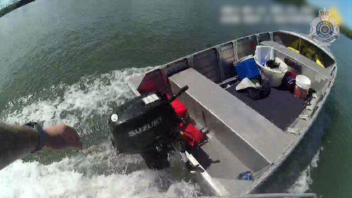 A still image taken from the Queensland police officer's body cam just before he leaps into the runaway tinny on the Calliope River.