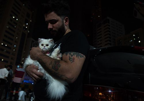 Syrian national Fadlallah Hassoun comforts his cat named Vodka after escaping a fire at a high-rise building in Sharjah