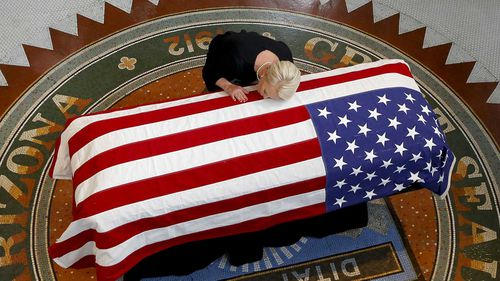 Cindy McCain rests her head on the casket of her late husband John.