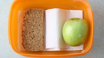 School lunch sparse orange lunch box with apple and slice