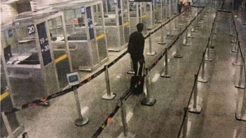 Santoro can be seen alegedly walking through the processing areas of an airport.
