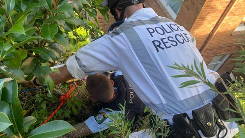 A member of NSW Police Rescue and a NSW Police officer attempt to rescue the man.