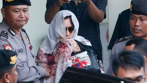 Australian Schapelle Corby is escorted by Bali Police at the parole office in Denpasar, Bali, Indonesia. (AAP)