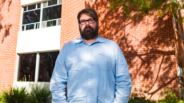 Chris Lambert, a musician and recording engineer stands in front of Muir Hall dormitory at California Polytechnic University.