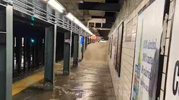 Floodwaters gush into a New York subway station.