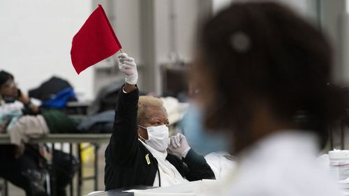 An election inspector waves a flag to call for assistance as ballots are counted into the early morning hours in Detroit, Michigan.