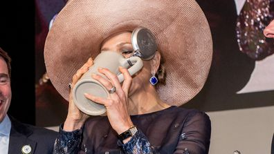 Queen Maxima of the Netherlands scolls beer from a tankard