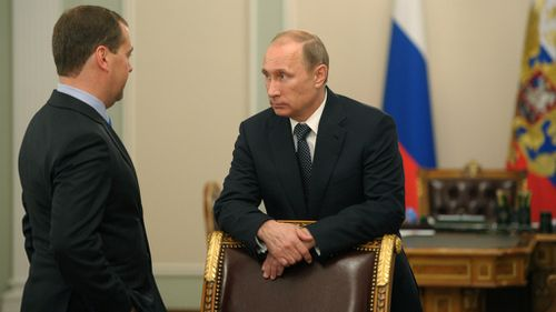Russian President Vladimir Putin speaks to Prime Minister Dmitry Medvedev after a moment of silence mourning the victims killed in the Malaysia Airlines plane crash on Thursday, July 17. (AP Photo)