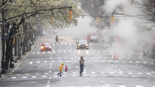 Light traffic frames a woman and child as they walk across Madison Avenue on March 29, 2020, in Midtown Manhattan of New York.