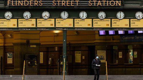A lone commuter walks out of Flinders Street station in Melbourne, Australia.
