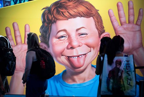The face of Alfred E. Neuman is framed by attendees at the DC booth during the first day of Comic-Con International at the San Diego Convention Center in San Diego.