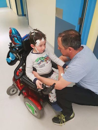 William in his power wheelchair, with is dad Ben.