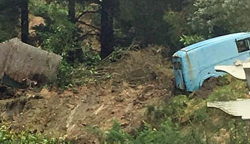 Vehicles were pushed down the slope after the landslide in Dunedin on Saturday. (Photo: Keith Kelsall).