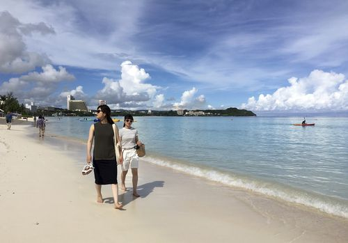 Tourists walk the beach in Tumon, Guam. (AAP)