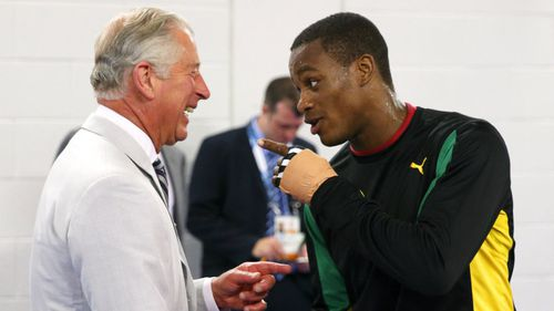 Prince Charles, Prince of Wales fake spars with Jamaican boxer Cheavon Clarke ahead of the start of the Commonwealth games.