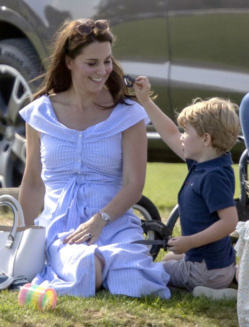 Prince George plays with a toy knife as he sits with his mother. Picture: AAP