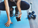 Woman working out with phone and dumbbells