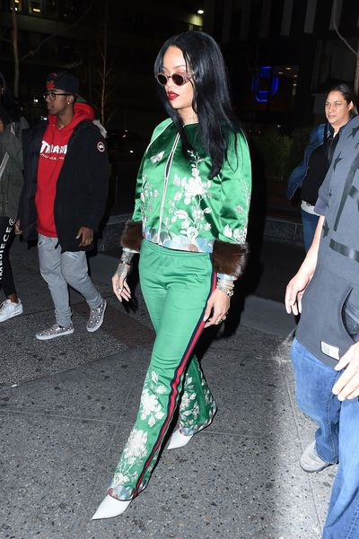 Rihanna takes the emerald silk tracksuit to sport couture levels with a bold red lip and a white pointed heel.