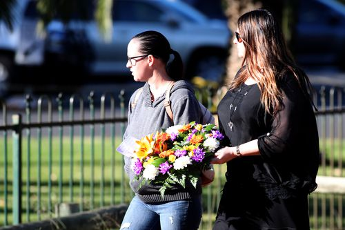 Mourners brought floral tributes to remember the family. (AAP)