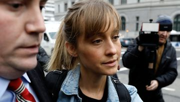 Actress Allison Mack exits federal court in Brooklyn, New York, after her arrest on charges of recruiting women into a sex trafficking operation.