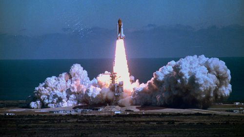 The shuttle Challenger rises on a pillar of flame, just moments before exploding in a ball of fire