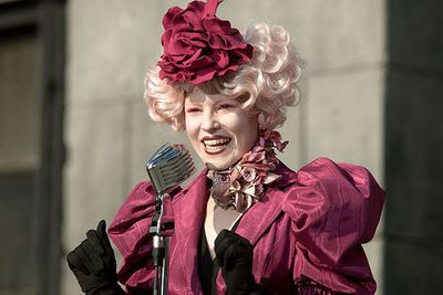 NOW: From playing her husband's chaperone to playing District 12's chaperone, Elizabeth Banks' most recent role comes in the form of Effie Trinket in <I>The Hunger Games: Mockingjay</i>.