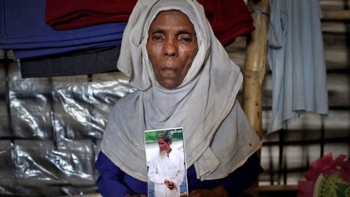 Kulilla Khatun, 65, holds up a laminated photograph of her late husband Nazir Ahmed, whom she says soldiers dragged away and decapitated with machetes. (Photo: AP).