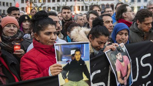 Relatives of those slain hold their photos at a vigil in Hanau, Germany.