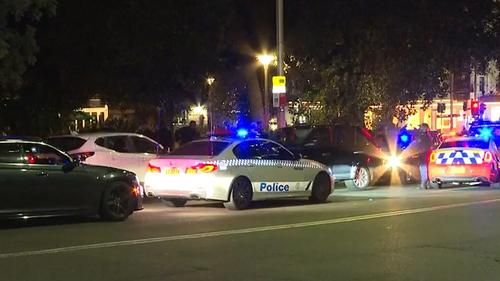 Police cars swarm the allegedly stolen black Range Rover.