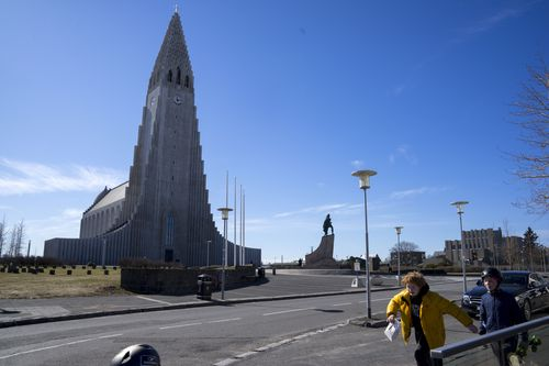 In this photo taken on Wednesday, April 29, 2020, two local boys walk past the the empty plaza of Hallgrimskirkja Church, a popular tourist destination in downtown Reykjavik, Iceland.