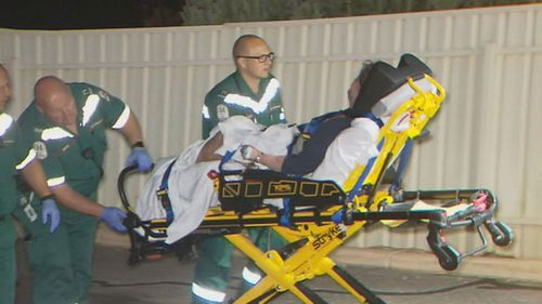 Ms Cox being taken to hospital for treatment after allegedly being attacked by a police dog.