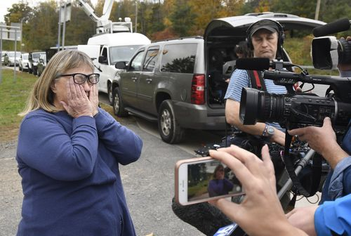 Barbara Douglas of Danamora, N.Y., reacts while talking about her four family members who died.