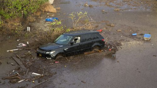 United States, California:A car is stuck as the deadly mudslides devastating Southern California. (AAP)